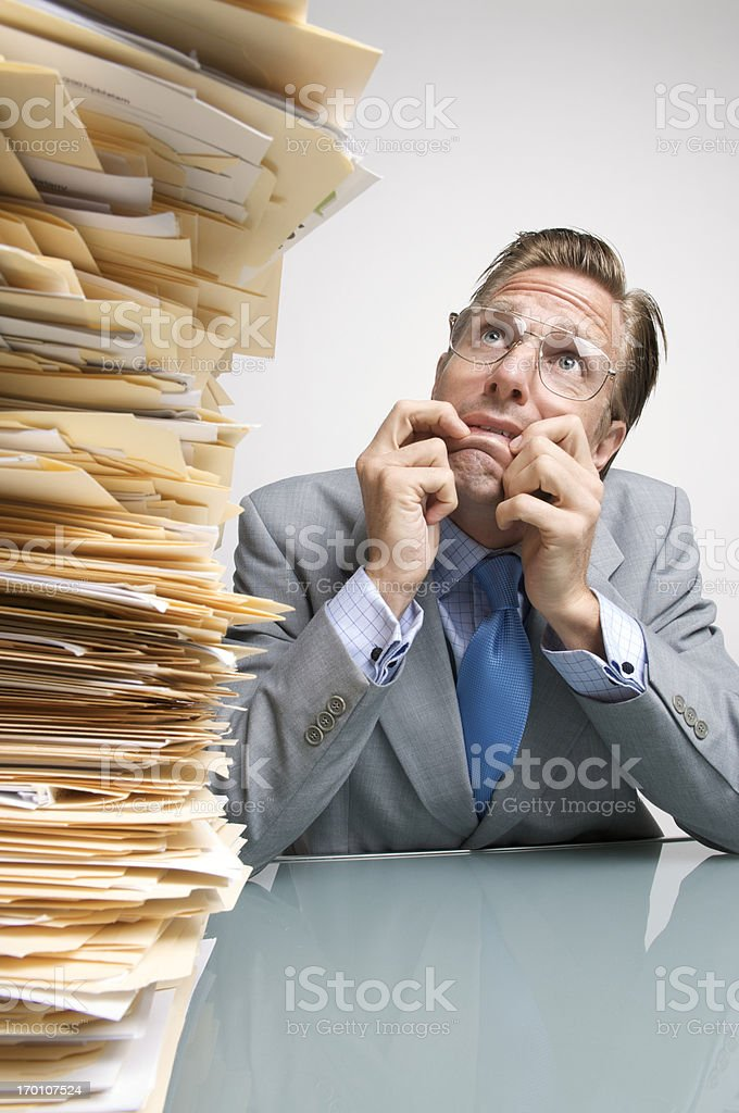 Overworked Office Worker Businessman Looking at Massive Paperwork Pile royalty-free stock photo