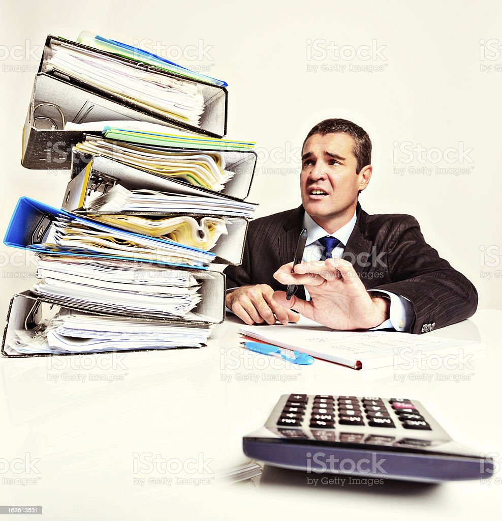 Overworked, stressed businessman looks at stack of files nervously royalty-free stock photo