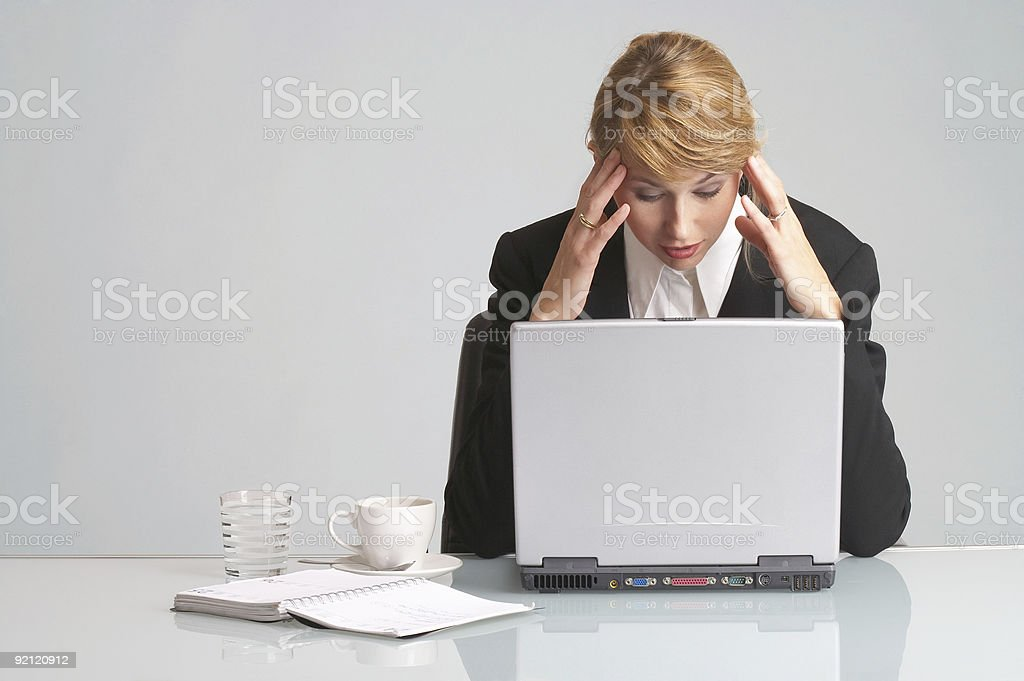 over-worked stressed businesswoman with laptop has headache stock photo