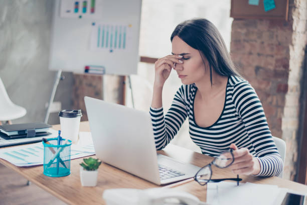 överarbetade trött sekreterare håller glasögon och vidrör hennes näsa bro - work stress bildbanksfoton och bilder