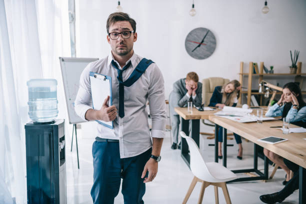 overworked untidy businessman with clipboard standing at office while colleagues sitting at conference hall stock photo