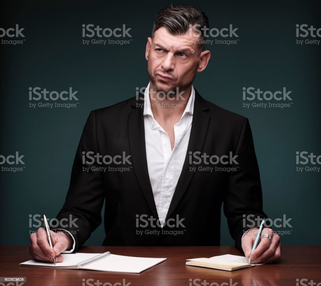 overworked writer uses two notebooks at once stock photo