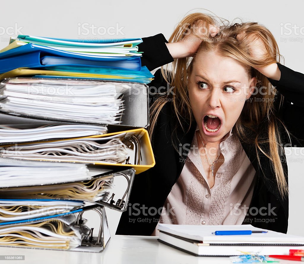 Overworked young businesswoman tearing hair out in frustrated anger royalty-free stock photo