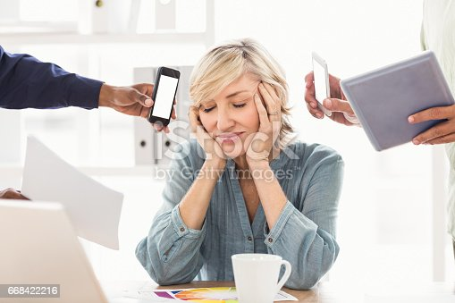 Overwrought businesswoman covering her ears at the office