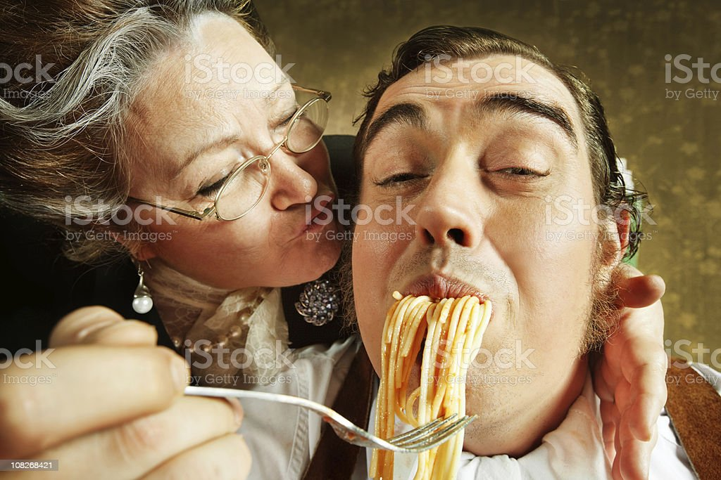 Overzealous Mother Feeding Adult Son Pasta stock photo