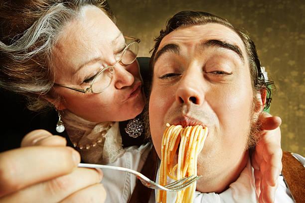 overzealous figlio adulto pasta madre nutrire - brunette woman eyeglasses kiss man foto e immagini stock