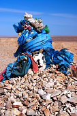 Shamanic ovoo, oboo or obo (ceremonial rock pile or cairn), covered with silk hadags or khadags (sacred blue scarves) and prayer flags in the Gobi desert in Mongolia.