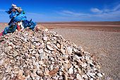 Shamanic ovoo, oboo or obo (ceremonial rock pile), covered with silk hadags or khadags (sacred blue scarves) and prayer flags in the Gobi desert in Mongolia.