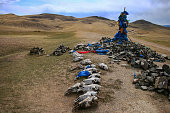 Ovoo oroboo, ceremonial rock pile or cairn, with sacred hadags or khadags, blue silk scarves and sheep skulls close to Erdene Zuu Khiid Monastery, part of the Orkhon Valley, UNESCO Cultural Landscape World Heritage Site, in Kharkhorin or Karakorum, Mongolia.