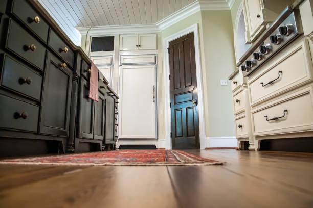ow uitzicht op keuken met hardhouten vloeren en aangepaste kasten en fornuis - laag camerastandpunt stockfoto's en -beelden