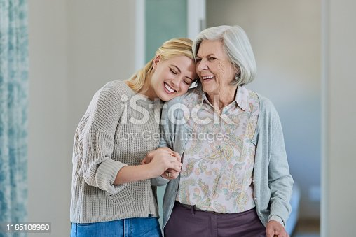 Cropped shot of an attractive young woman holding her happy senior mother while walking through the nursing home