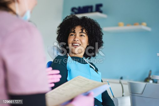 Shot of a young woman having a consultation with her patient in a dentist's office