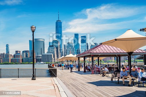 People relax during lunchbreak at J Owen Grundy Park at the Jersey City waterfront on a sunny day with the Manhattan skyline in the background.