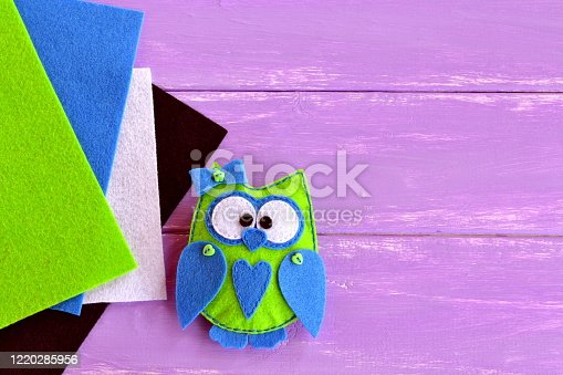 istock Owl toy is sewn from plush felt. Green fabric owl with blue heart and bow. Home decor idea for beginners and children. Frugal and fun hobby. Colored felt sheets on a wooden table 1220285956