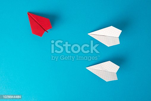 Red paper plane is flying its own route on blue background where two other white paper planes are flying straight to the left.