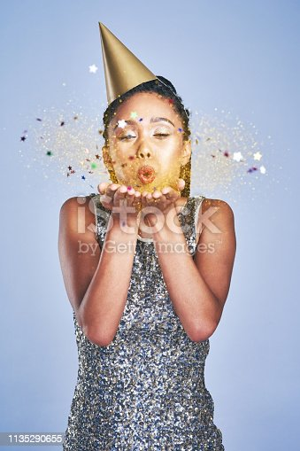 Shot of a young woman wearing a party hat and blowing confetti against a blue background