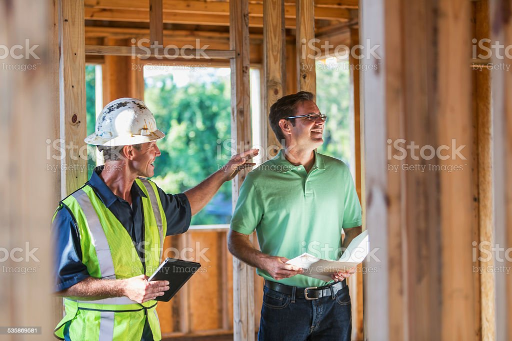 Owner and worker inspecting house under construction stock photo