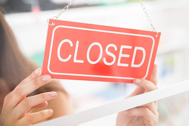 owner holding closed sign in clothing store - closed stock photos and pictures