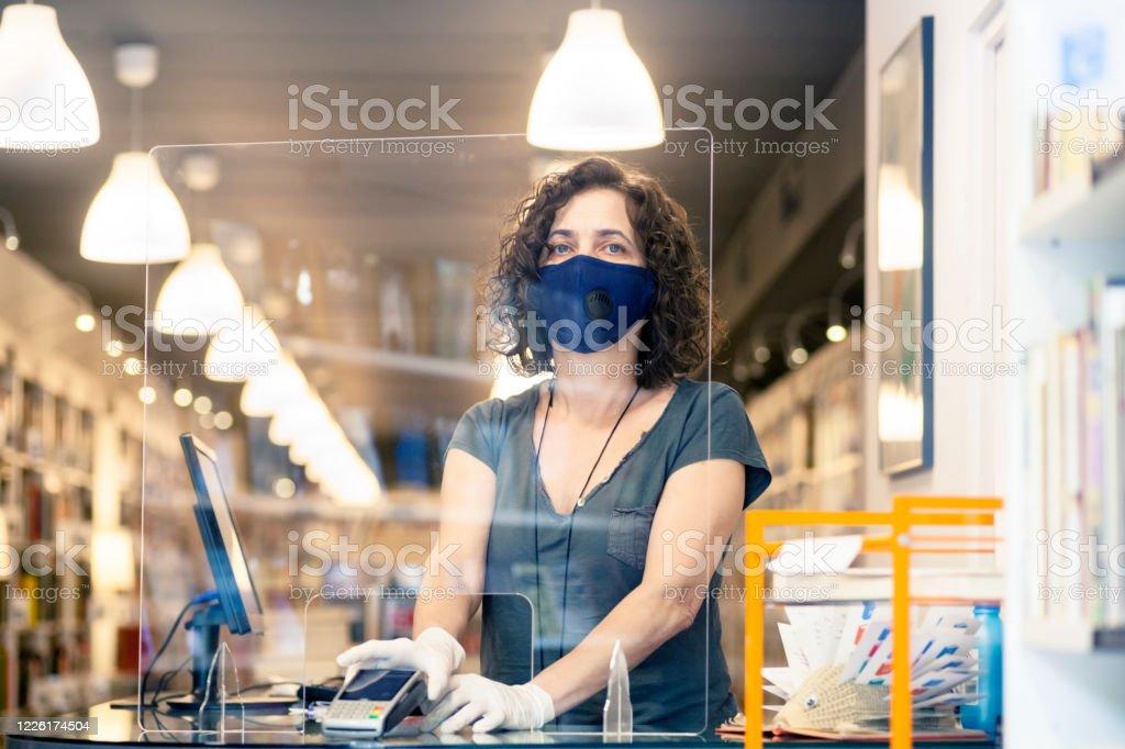 Eigenaar in de boekhandel tijdens covid - Royalty-free Aankoop met creditcard Stockfoto