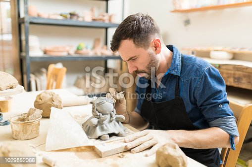 Confident male owner making clay sculpture of doll at workbench in workshop