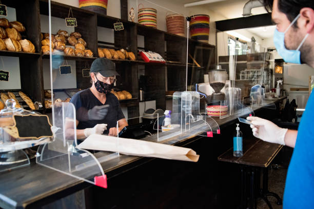 Owner of bakery shop wearing mask serving a customer. stock photo