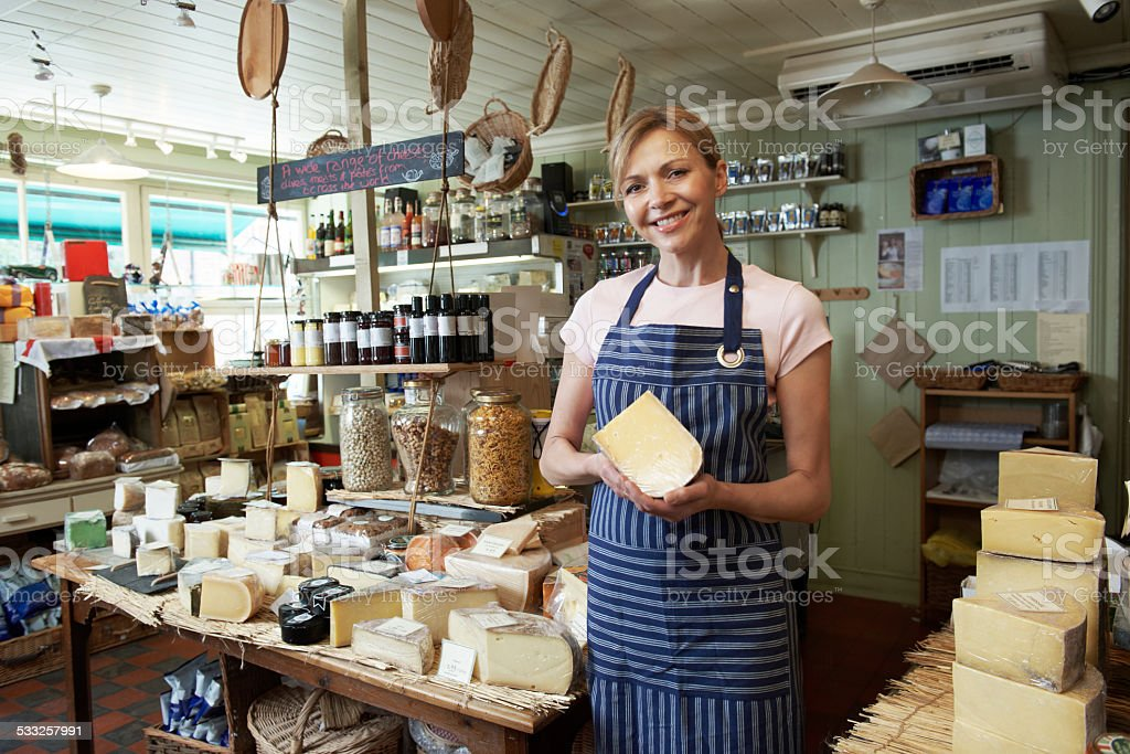 Owner Of Delicatessen Standing In Shop Holding Cheese stock photo