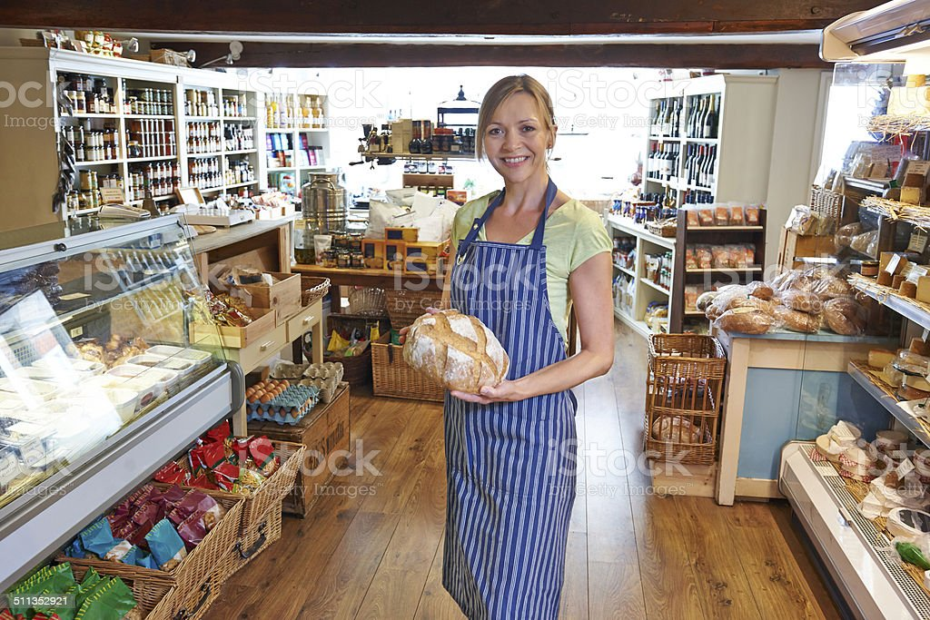 Owner Of Delicatessen Standing In Shop Holding Loaf Of Bread stock photo