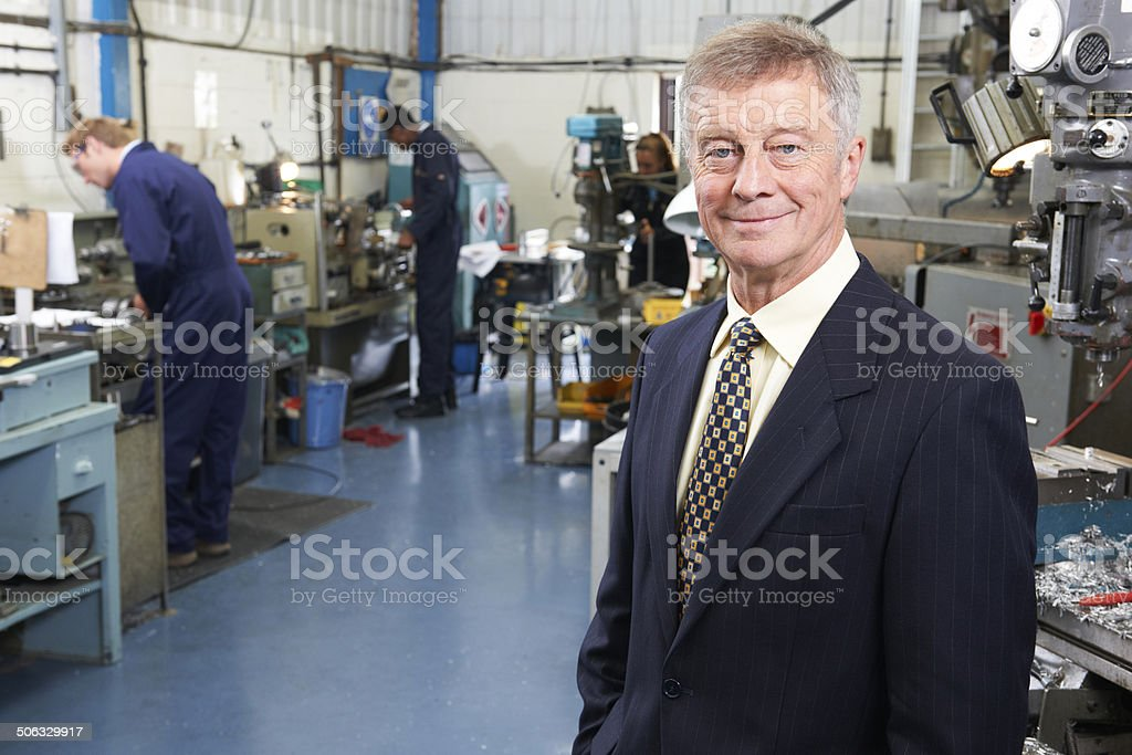 Owner Of Engineering Factory With Staff In Background stock photo