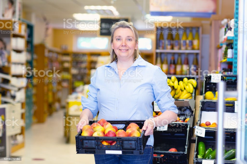 Owner Of Health Food Store Holding Box With Apples Stock