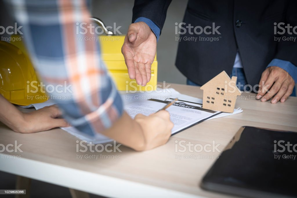 Owner of home signing contract after architect build home...