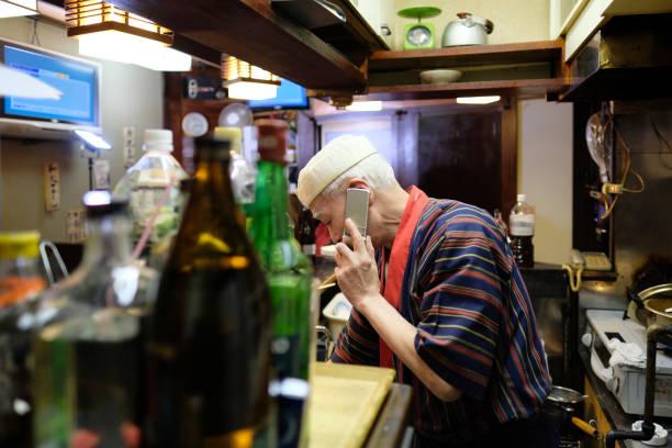 Owner of Izakaya, Japanese pub Snap shot of owner of Izakaya, Japanese pub old man working in a pub stock pictures, royalty-free photos & images