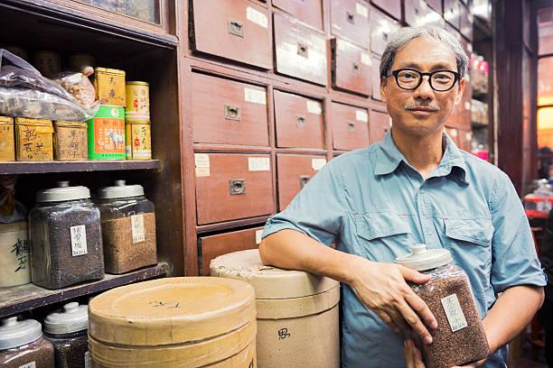 eigentümer der traditionellen chinesischen medizin shop in kowloon hongkong - teeladen stock-fotos und bilder