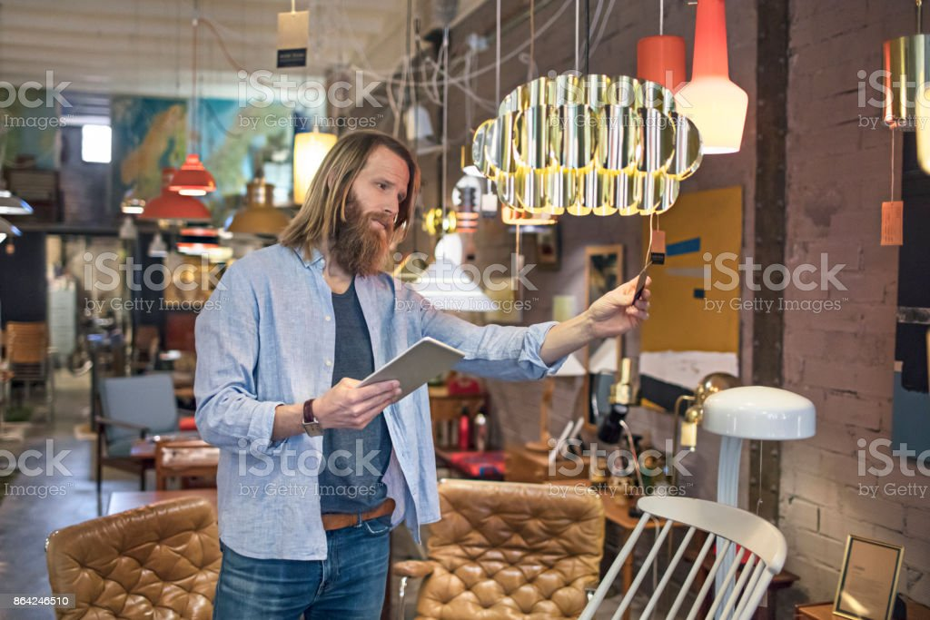 Owner organising catalog with digital tablet in furniture store royalty-free stock photo