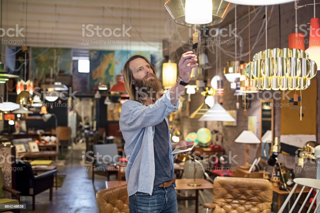Owner reading tag on lighting equipment in store royalty-free stock photo