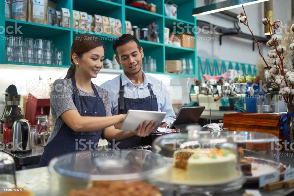 Owner showing digital tablet to colleague in cafe stock photo