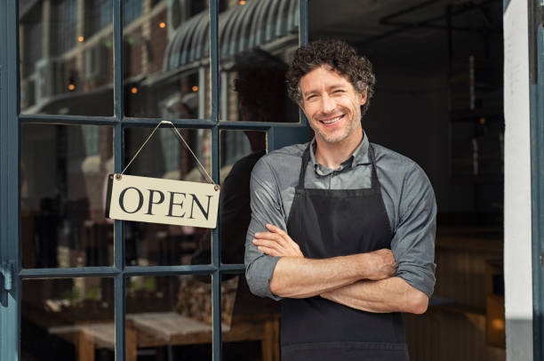 owner standing outside restaurant - owner stock pictures, royalty-free photos & images