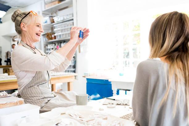 besitzer ein foto ihrer werkstatt - porzellan schmuck stock-fotos und bilder
