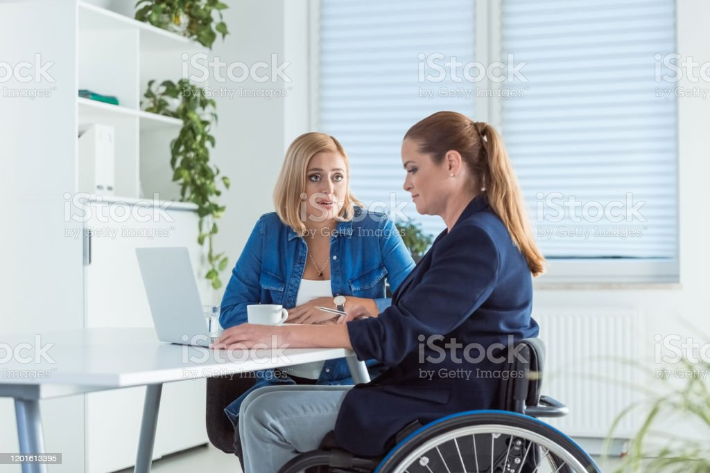 Owner talking to disable coworker on wheelchair Female executive talking with disable colleague on wheelchair. Entrepreneurs are planning new business strategies. They are working together in office. 40-44 Years Stock Photo