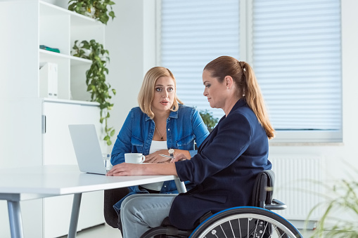 Owner Talking To Disable Coworker On Wheelchair Stock Photo - Download Image Now