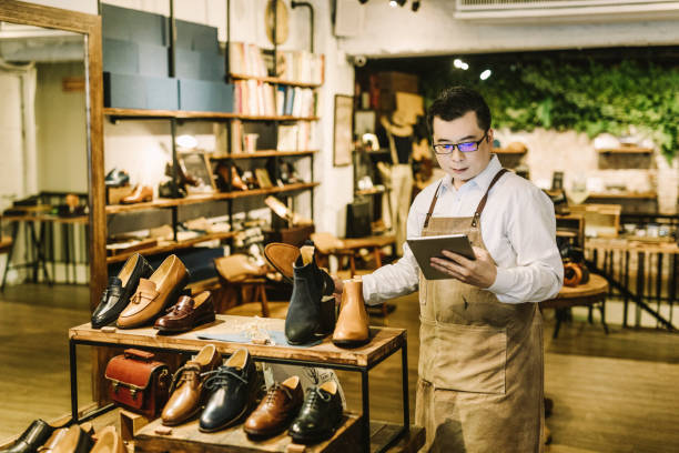 Owner using digital tablet while working in store stock photo