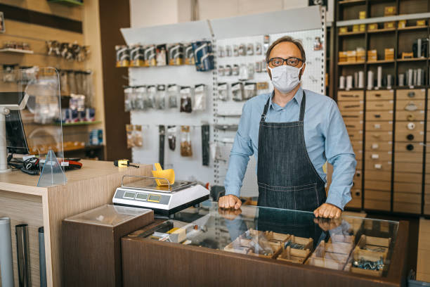 Owner with protective face mask at checkout stock photo