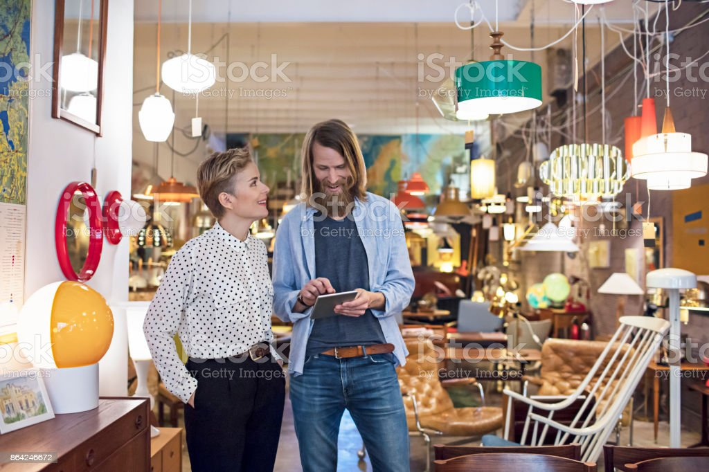 Owners using digital tablet in furniture store royalty-free stock photo