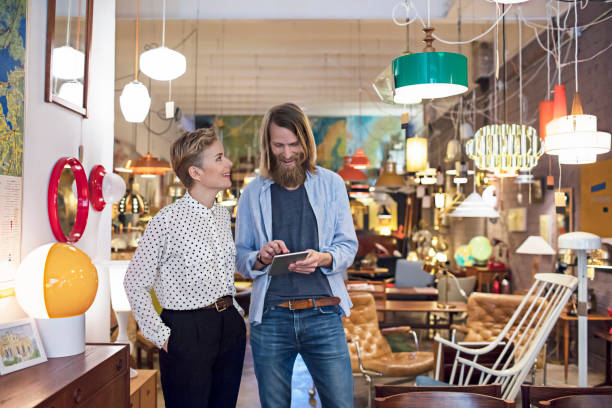 owners using digital tablet in furniture store - furniture shopping stock photos and pictures
