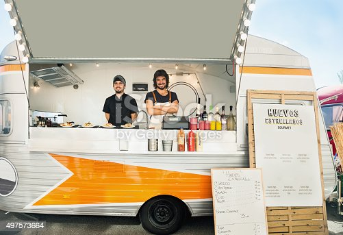 Owner and cook posing inside their food truck, parked in the street.