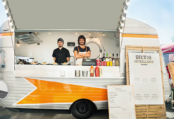 Owning a food truck Owner and cook posing inside their food truck, parked in the street. rv interior stock pictures, royalty-free photos & images