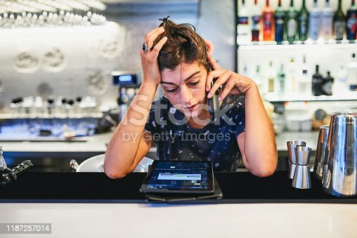 Shot of a young woman looking stressed while using a phone behind the counter of a bar