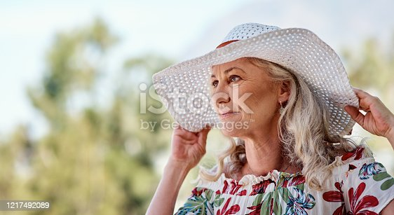 Cropped shot of an attractive senior woman standing outdoors on a summer's day