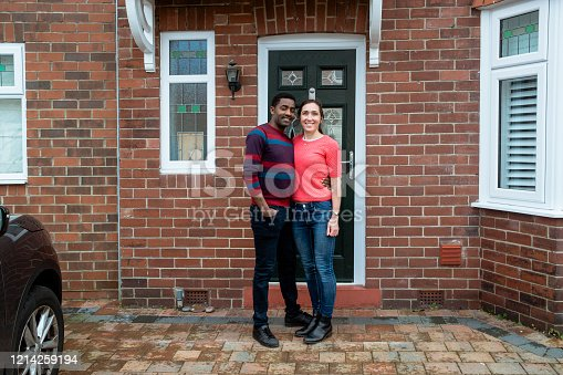 A full length portrait of an Ethiopian man and his Caucasian wife stood outside the front door of their new home.