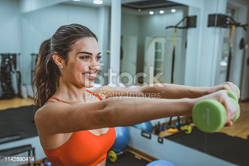Photo of Young woman doing exercise with dumbbell in gym. Happy fitness woman lifting dumbbells smiling cheerful, fresh and energetic. Caucasian fitness girl training. Close-up of a young woman exercising with weights in the gym. Beautiful fitness woman with lifting dumbbells . Sporty girl showing her well trained body . Well-developed muscles by strength training