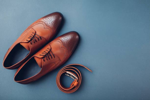 Oxford male brogues shoes with accessories. Men's fashion. Classical brown leather footwear with belt. Space